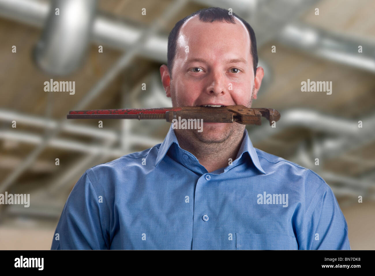 Young heating and sanitary craftsman with a pipe wrench in his mouth - Stock Image