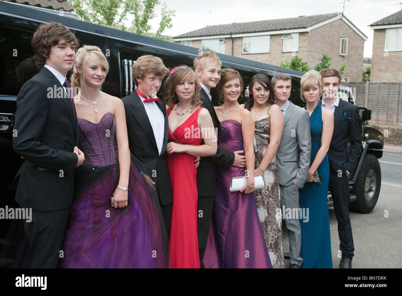 e321b4bbbf5 A group of teenage girls and boys dressed up ready for their school prom  posing in