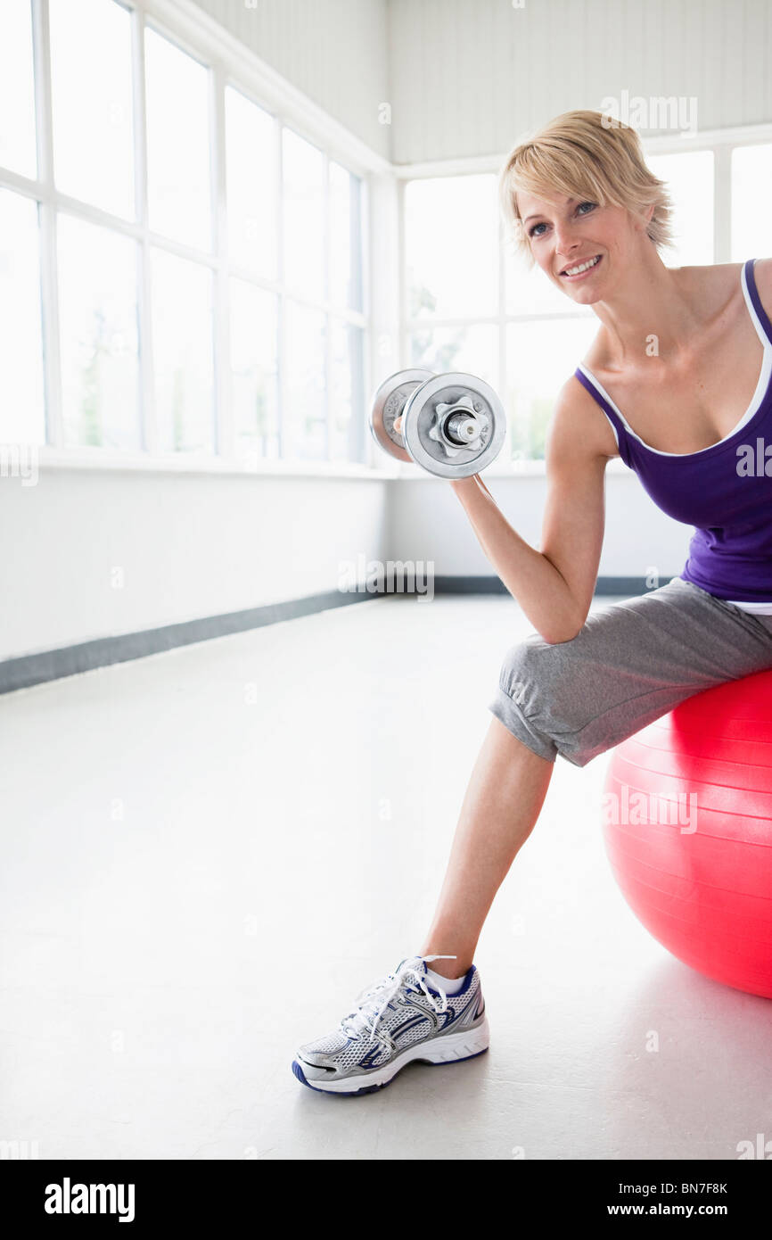 Woman with dumbbell sitting on gymball - Stock Image