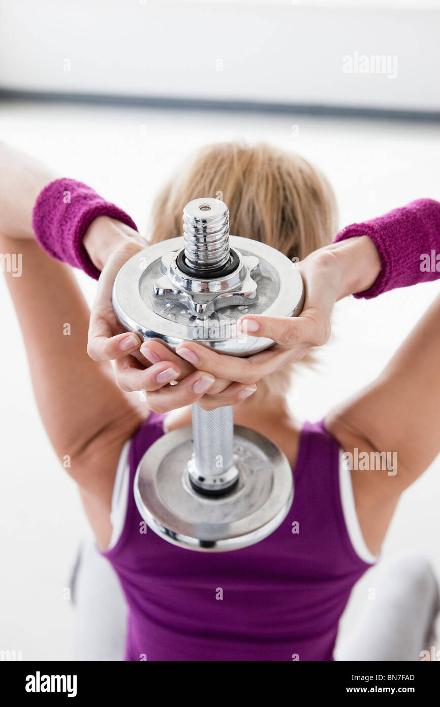 Woman with dumbbell training shoulders - Stock Image