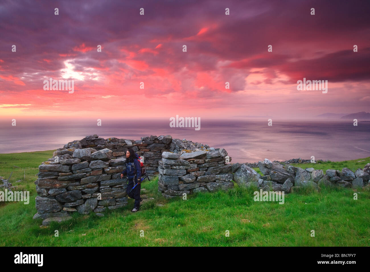 Colorful skies at sunset, and old stone shelter at the island Runde on the Atlantic west coast of Norway. - Stock Image