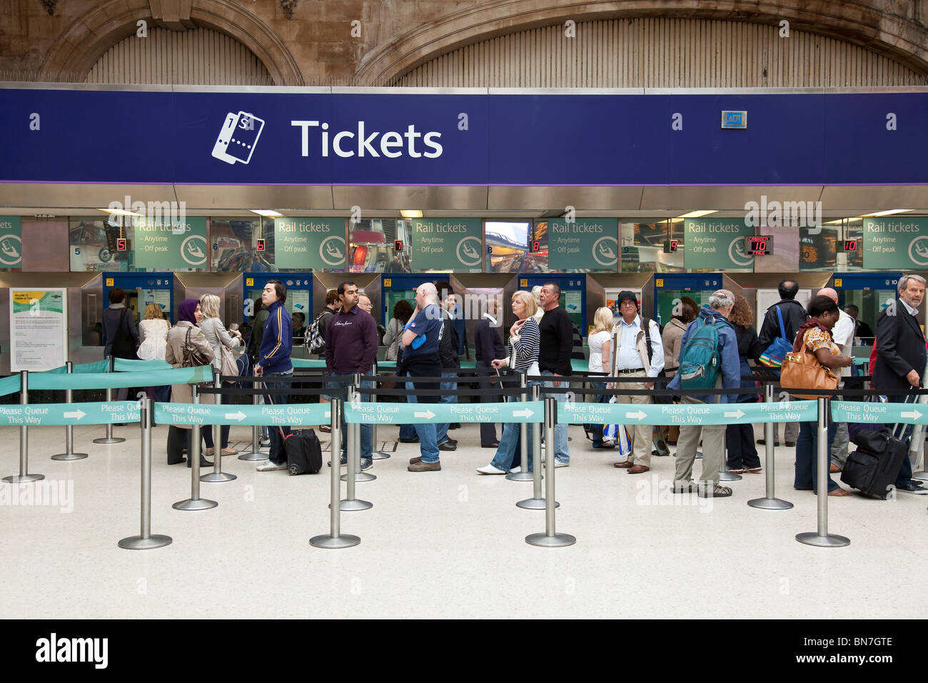 People waiting in a queue to by railway tickets in Victoria Station, London - Stock Image