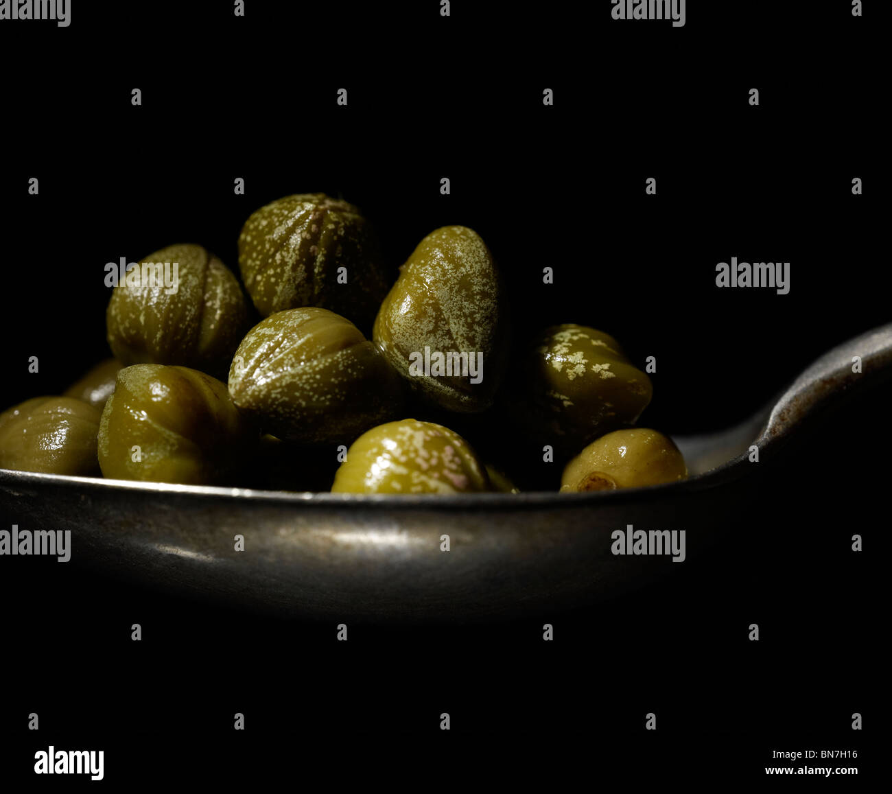 Close up of Capers on a spoon. Capers use dates back to more than 3000 BC. - Stock Image