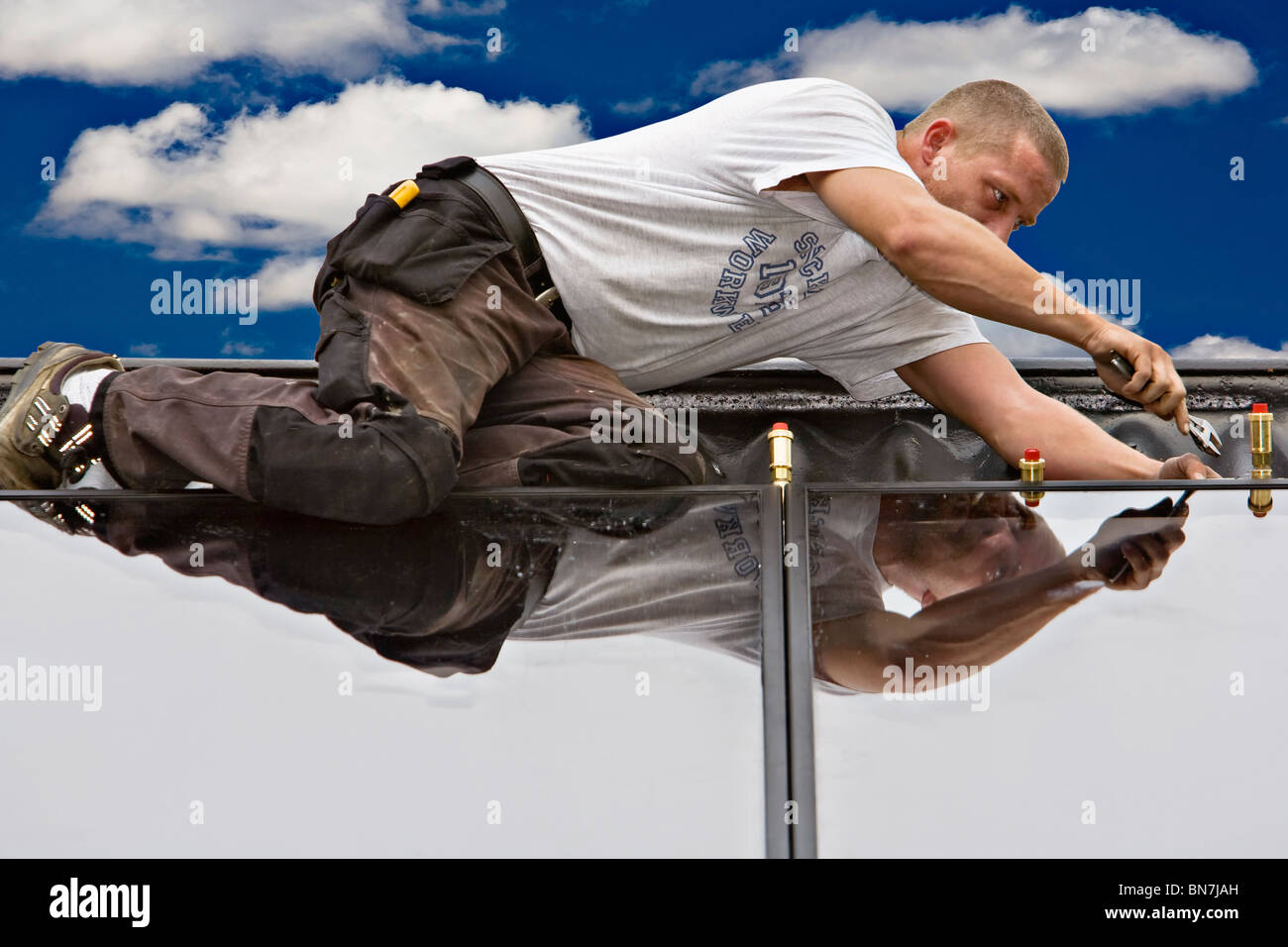 A heating and sanitary craftsman connecting the solar panels - Stock Image