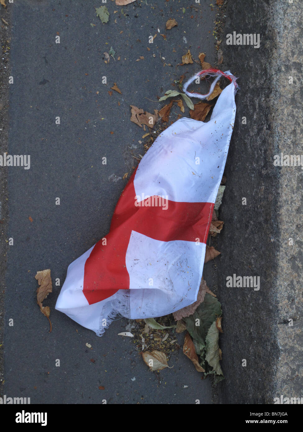 London July 2010.World cup England flag discarded in the gutter after England was defeated by Germany at football - Stock Image