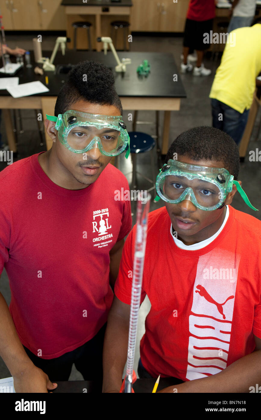African-American high school boys in safety goggles observe solution in a graduated cylinder during titration in Stock Photo