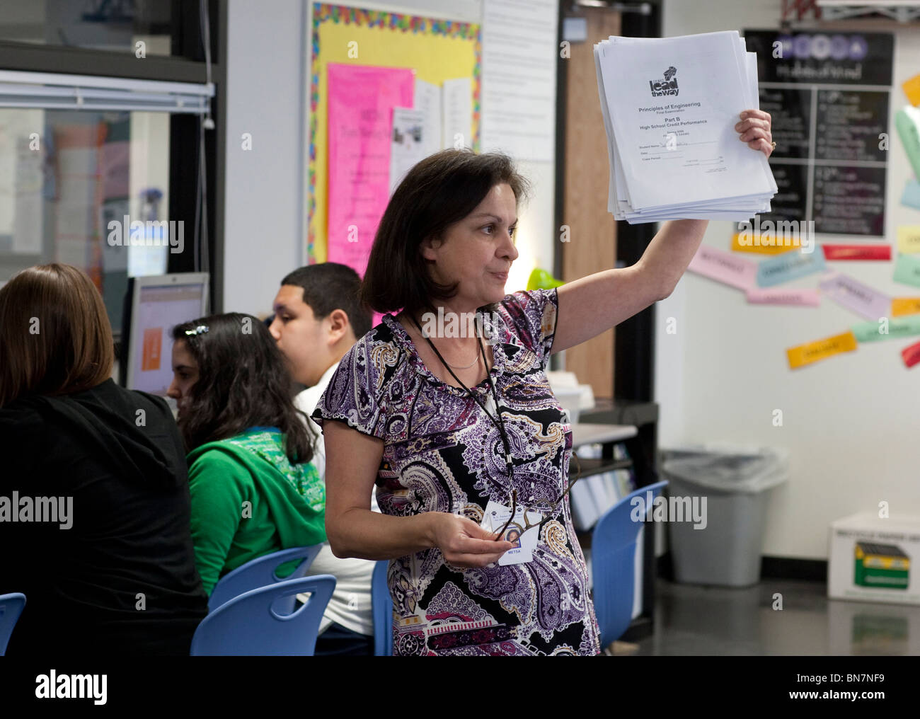 Anglo female high school engineering teacher holds up final exams in classroom Stock Photo