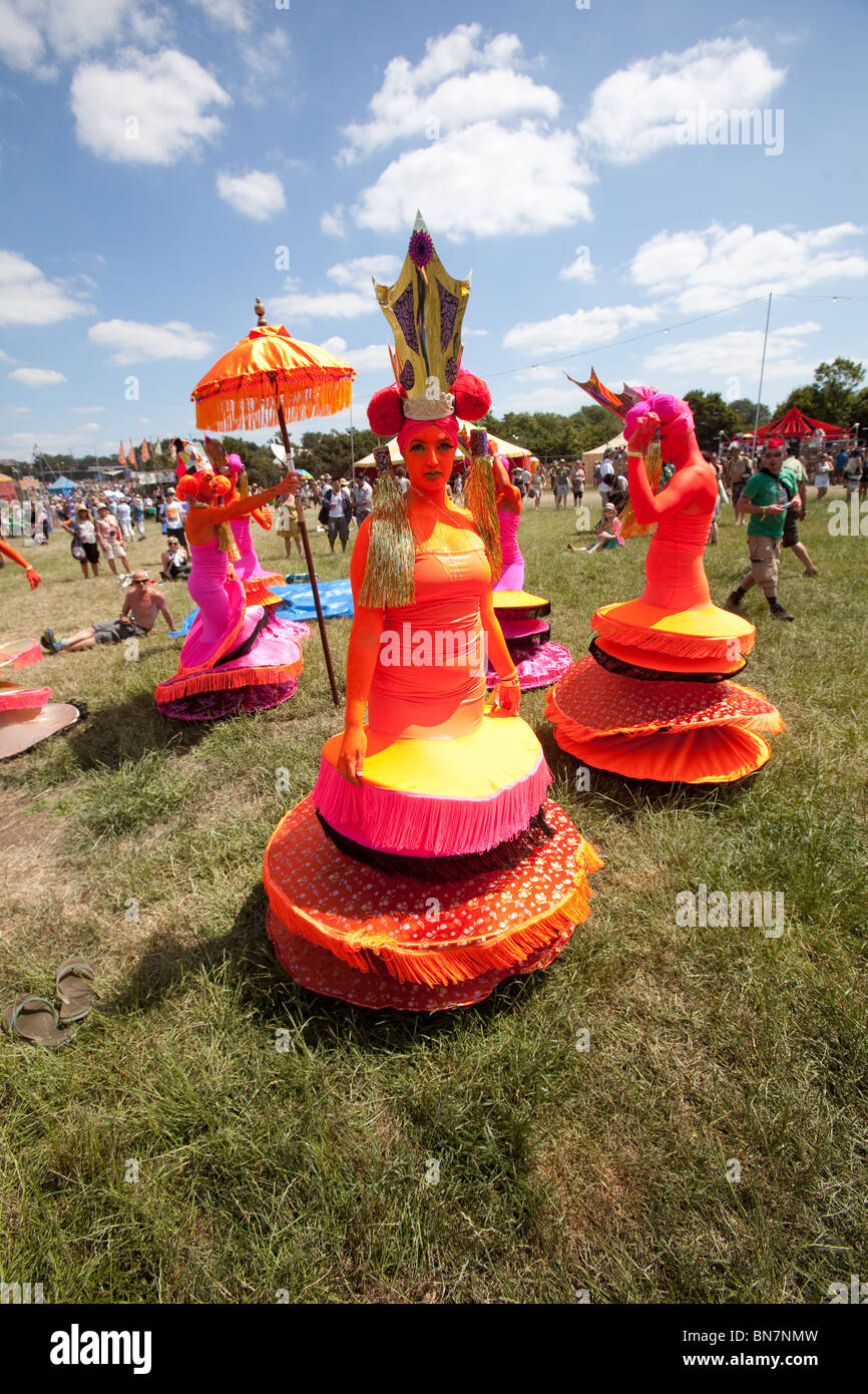 Bright orange cabaret performers in the circus field at the Glastonbury Festival 2010 - Stock Image