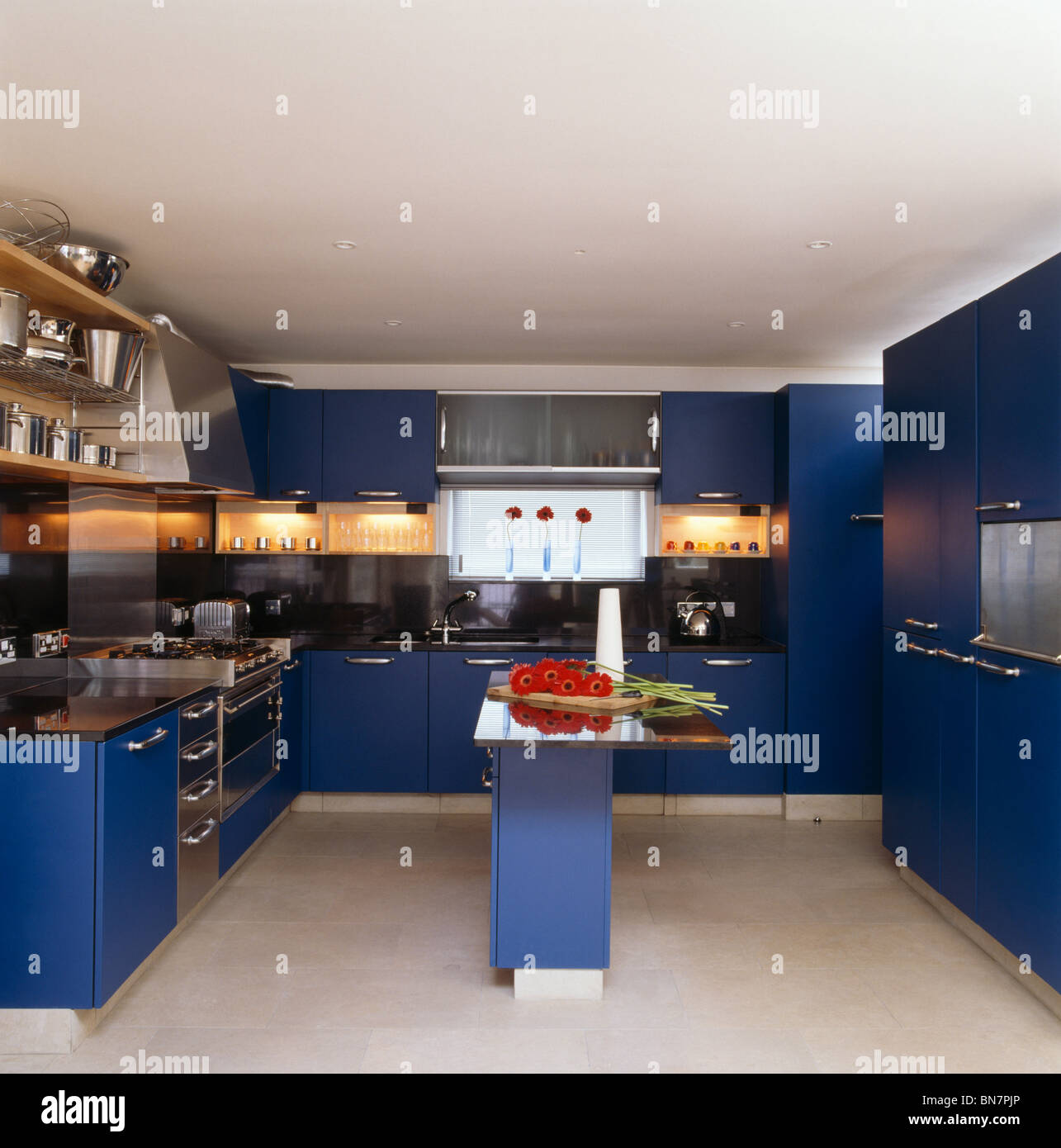 Bright blue fitted units in modern white kitchen with island unit and recessed lighting below wall cupboards - Stock Image