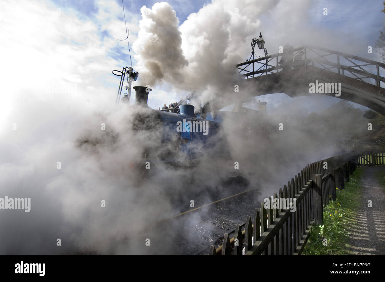 A steam locomotive train puffs under a footbridge at Haverthwaite station in the Lake District, Cumbria England - Stock Image