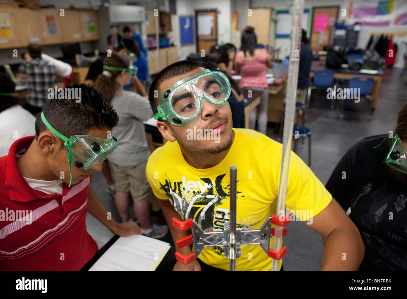Students in safety goggles do an experiment in chemistry class at the Math, Engineering, Technology and Science Stock Photo