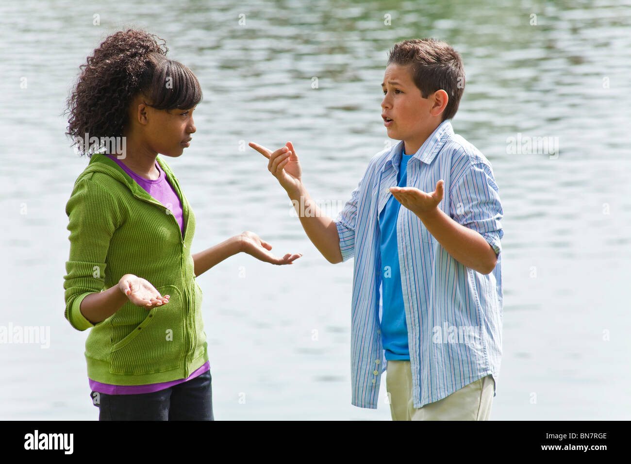 Ethnically diverse teen teenage kids hanging out talking with enthusiasm and hand gestures. MR ©Myrleen Pearson - Stock Image