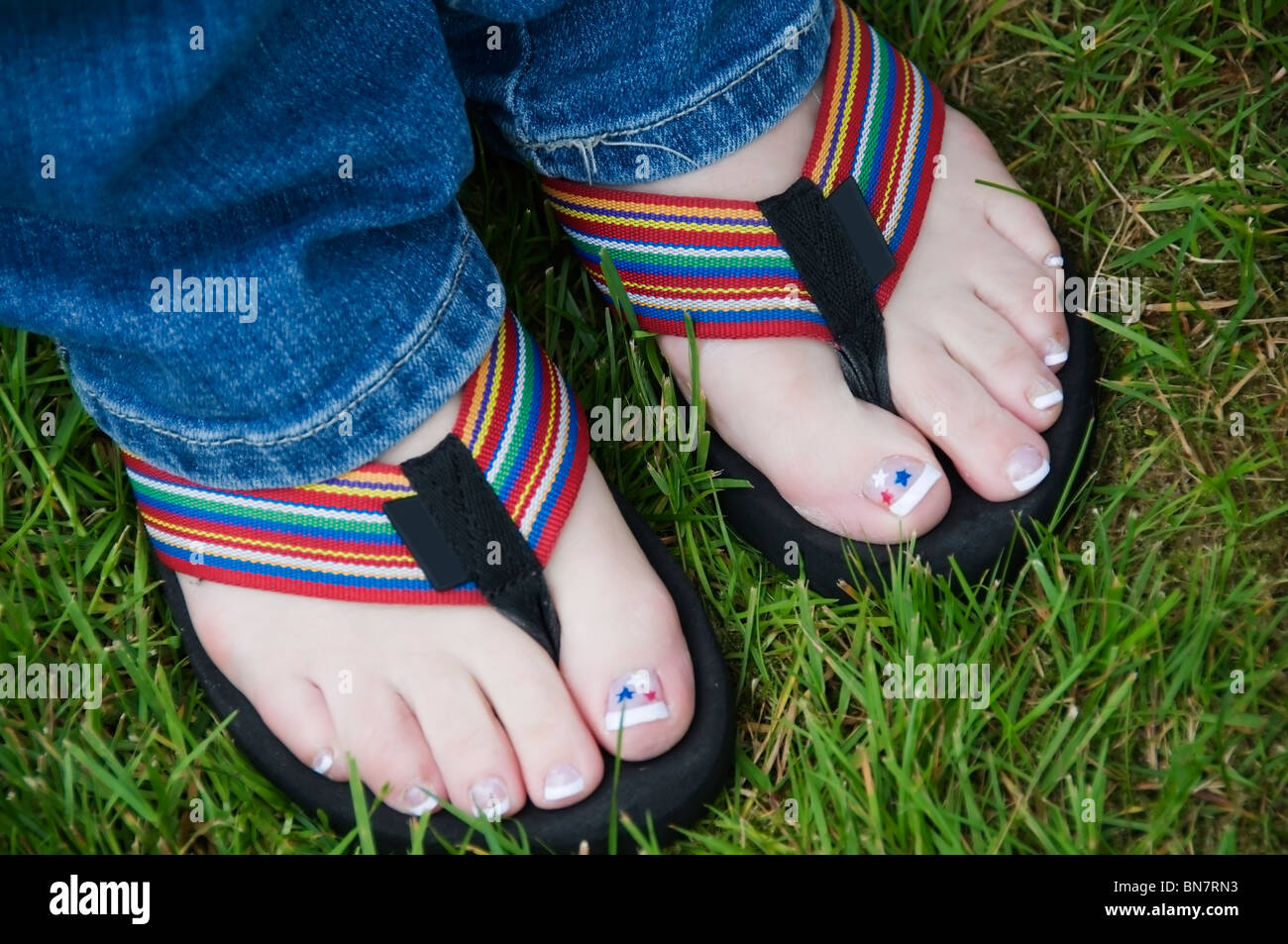Pedicured toes show off red, white, and blue star decals in colorful flip flops on the 4th of July. Stock Photo
