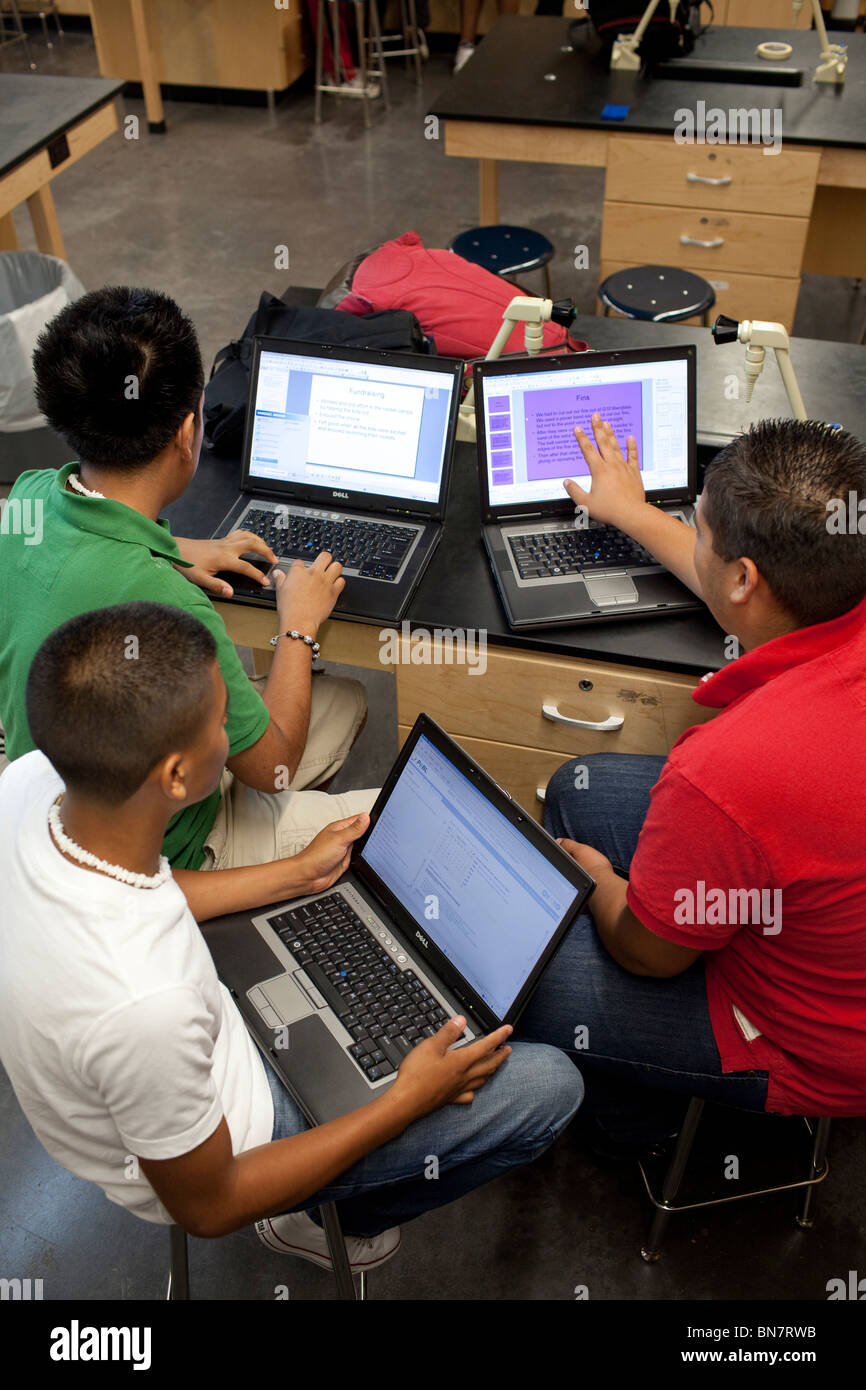 Hispanic high school boys work on assignment together using laptop computers in class. Stock Photo