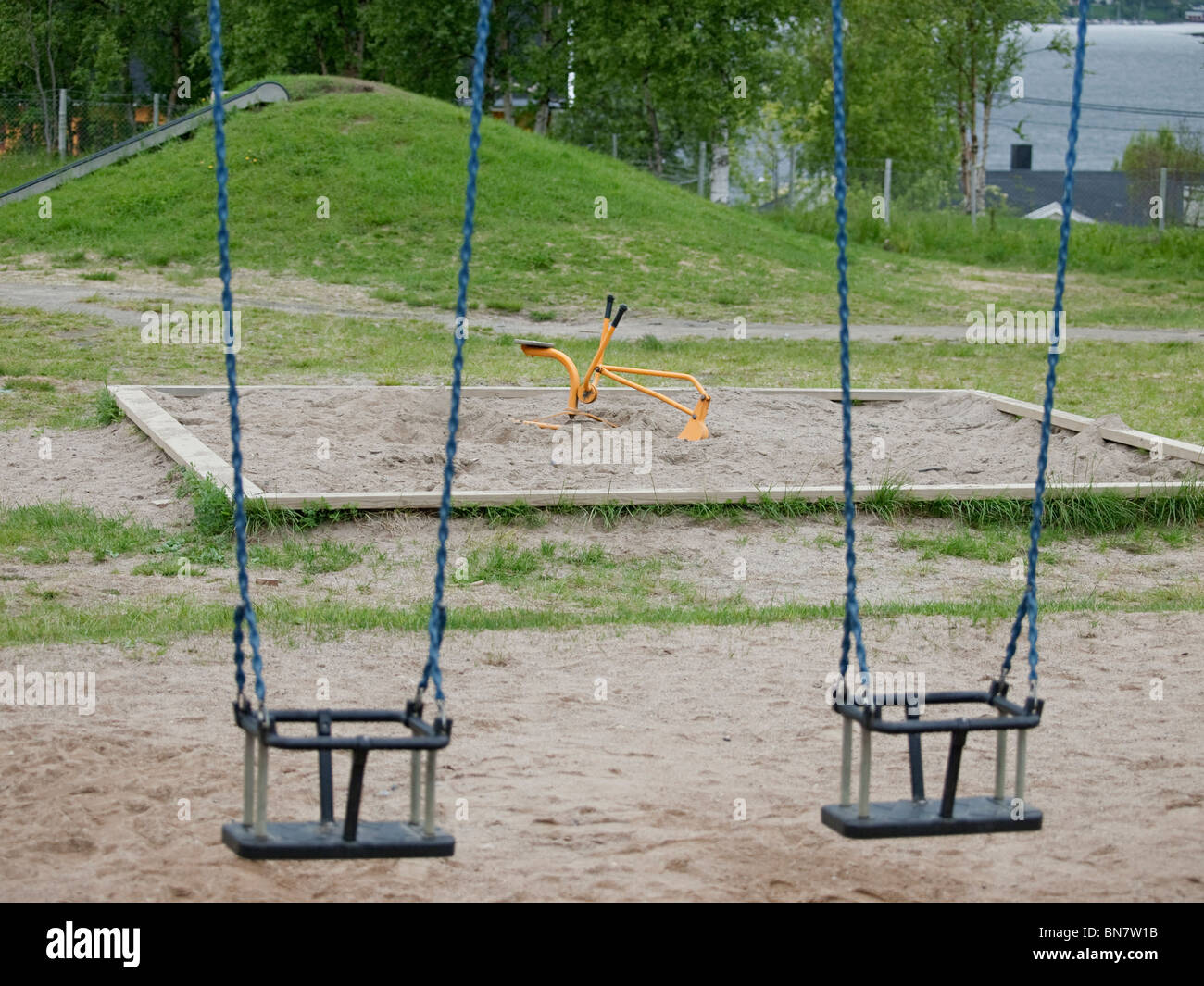 Swings in a playground blurred with a toy digger in the background. - Stock Image