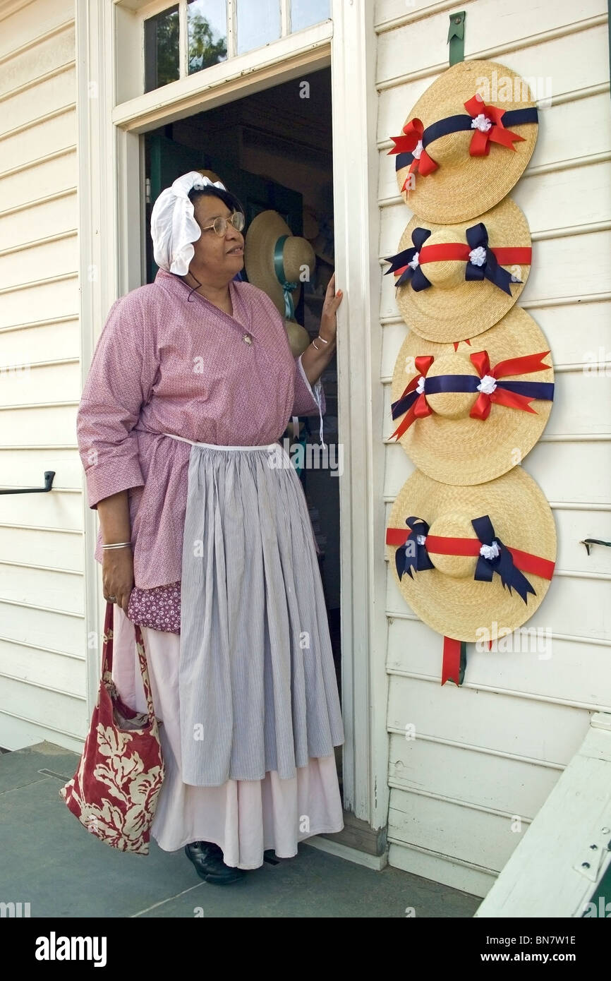 A costumed milliner shows off ladies' straw hats with red, white and blue ribbons outside a millinery shop in - Stock Image