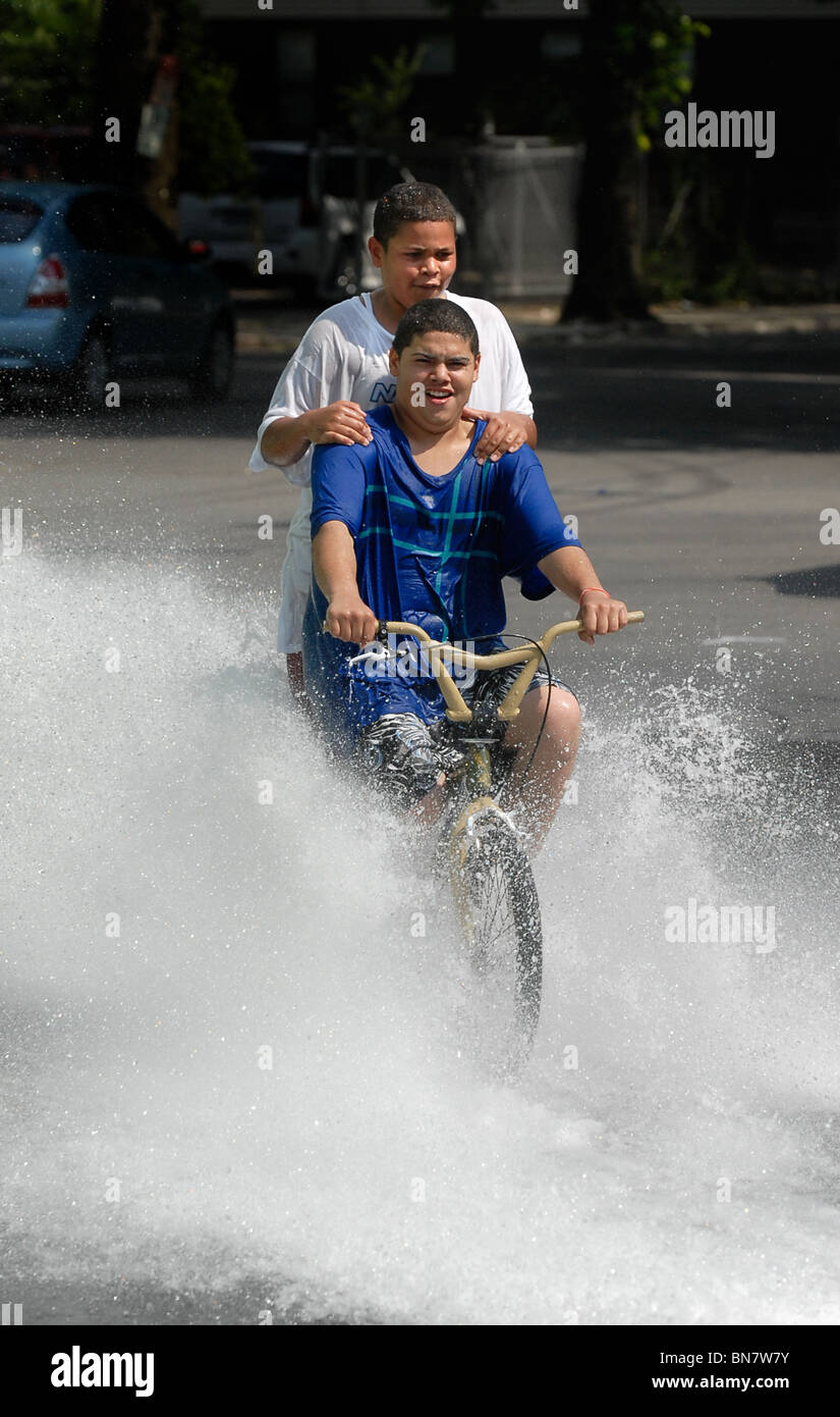 A Young teen rides through the spray of an open fire hydrant during a heat wave in New Haven CT USA where temps - Stock Image