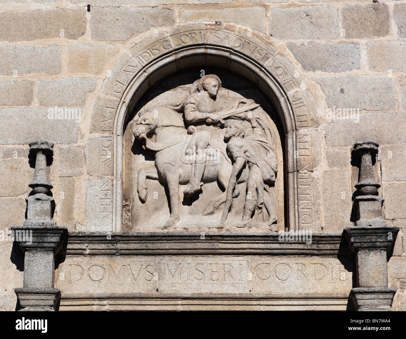Avila, Avila Province, Spain. Bas-relief of Saint Martin of Tours cutting his cloak in half to share with a beggar, - Stock Image