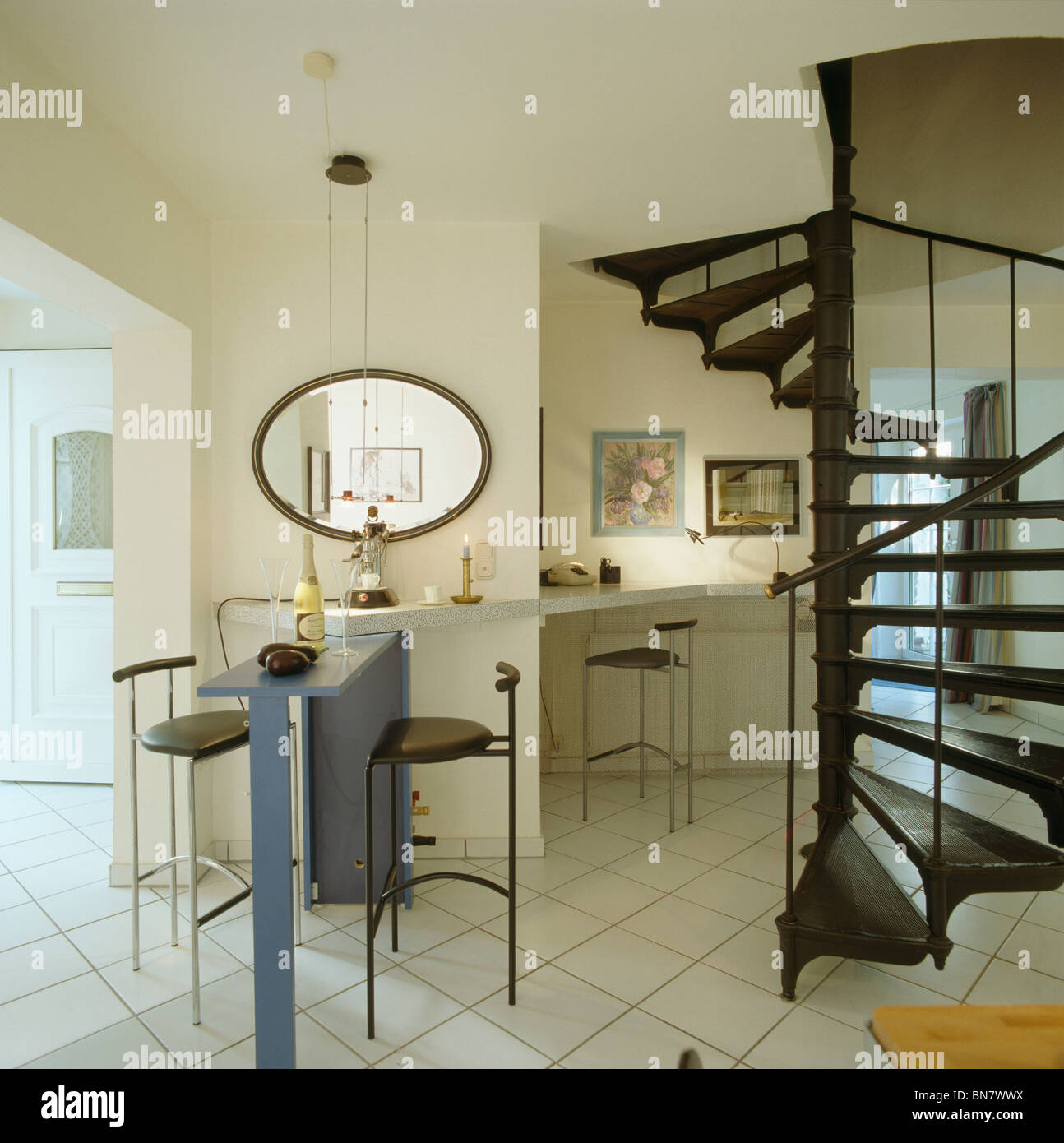 Black Spiral Staircase And White Tiled Flooring In Modern Open Plan Kitchen  With Metal Stools