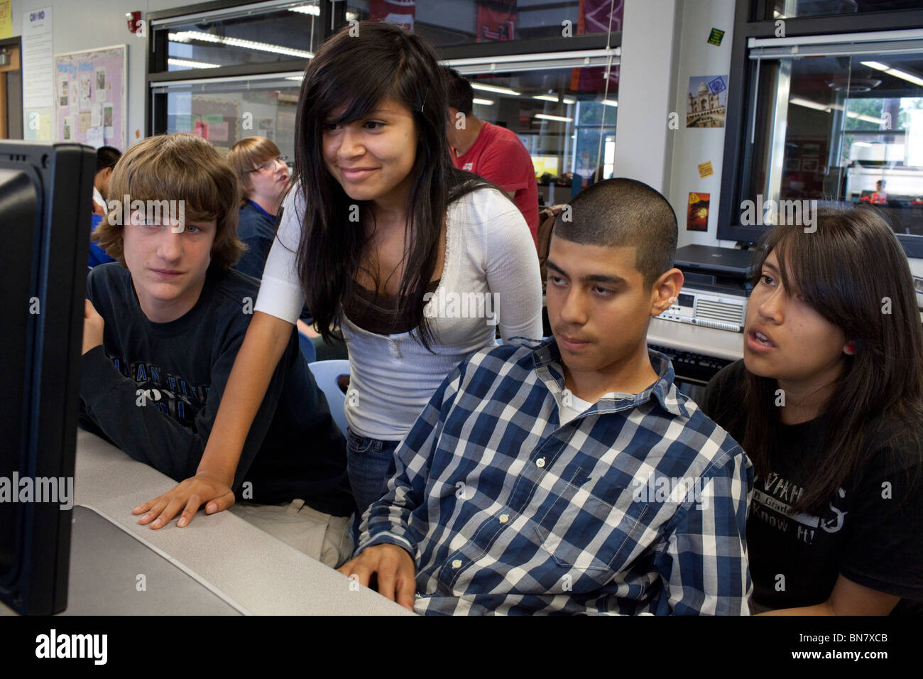 Male and female high school students look at computer monitor during class. Stock Photo
