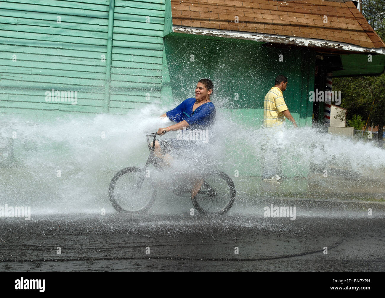 A Young teen rides through the spray of an open fire hydrant during a heat wave in New Haven CT USA where temps Stock Photo