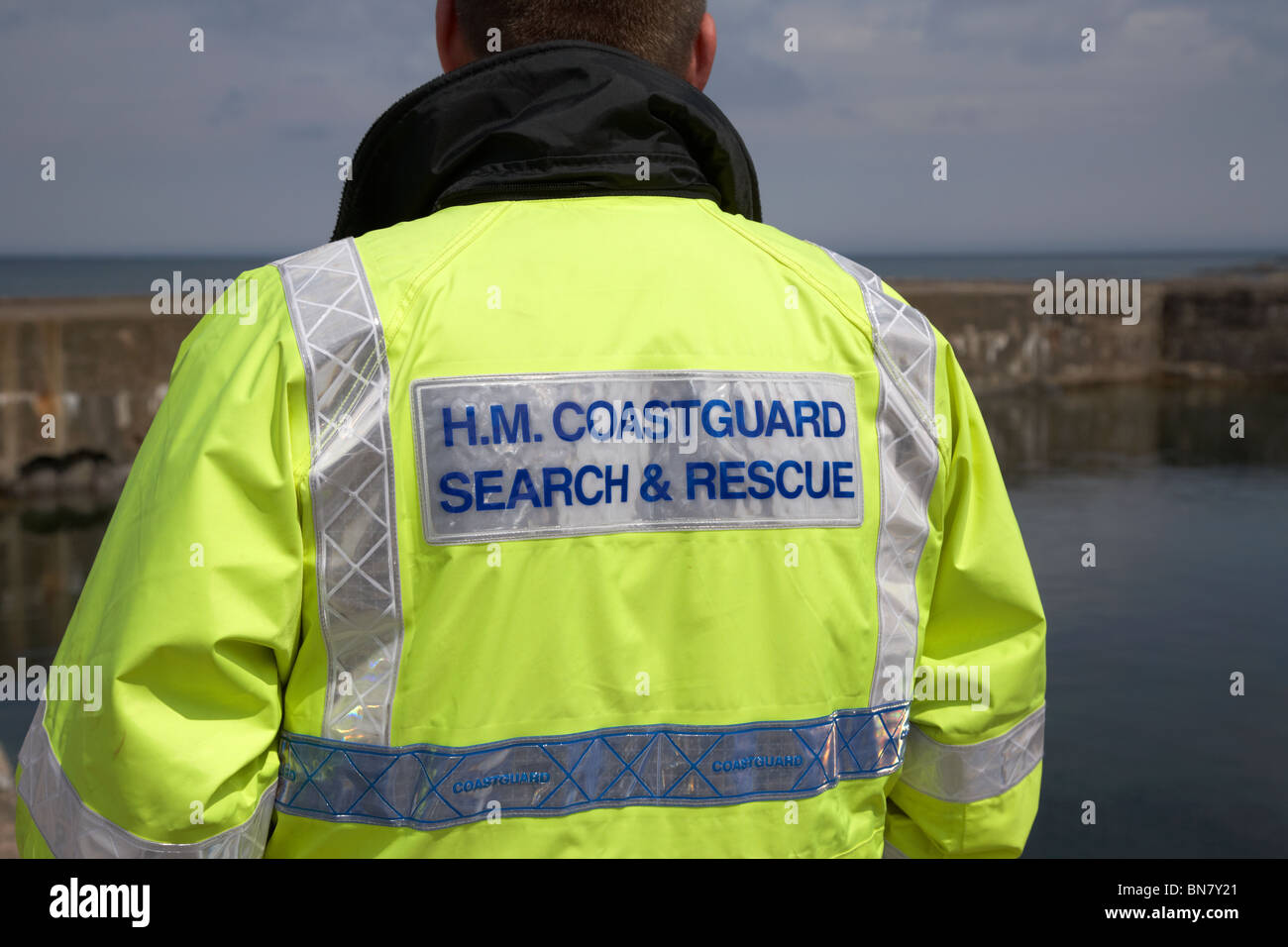 HM Coastguard search and rescue personnel wearing hivis jacket watching near the sea in the uk - Stock Image