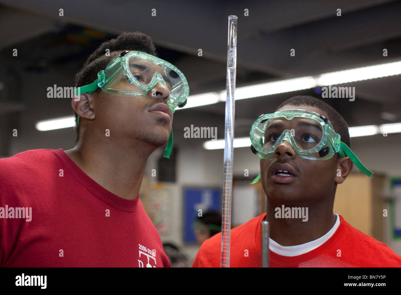 Male high school students wearing safety goggles perform a titration experiment using graduated cylinder during Stock Photo
