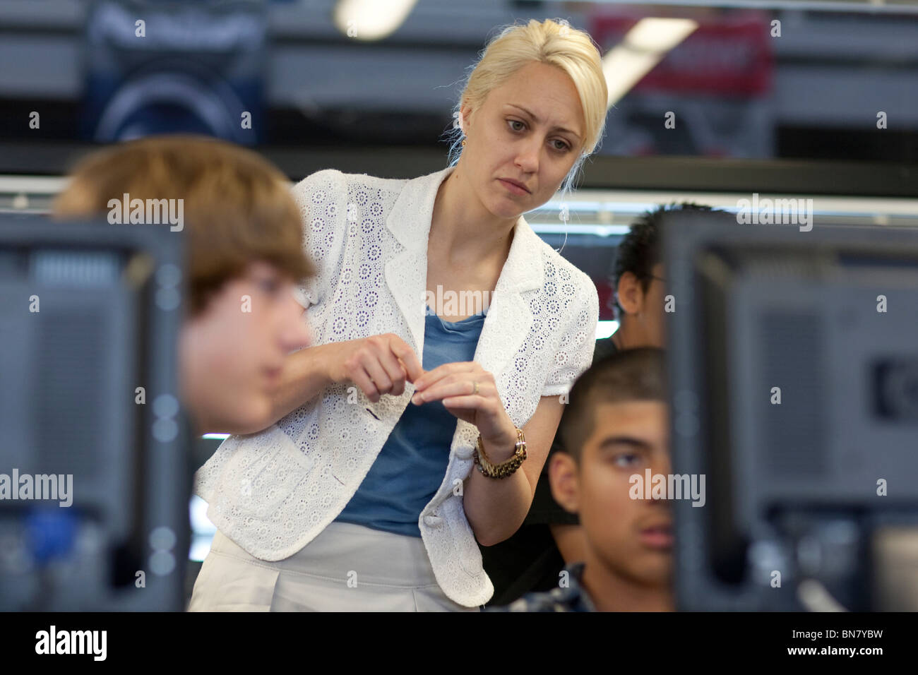 Anglo female high school English teacher reviews male student's work on his computer monitor. Stock Photo