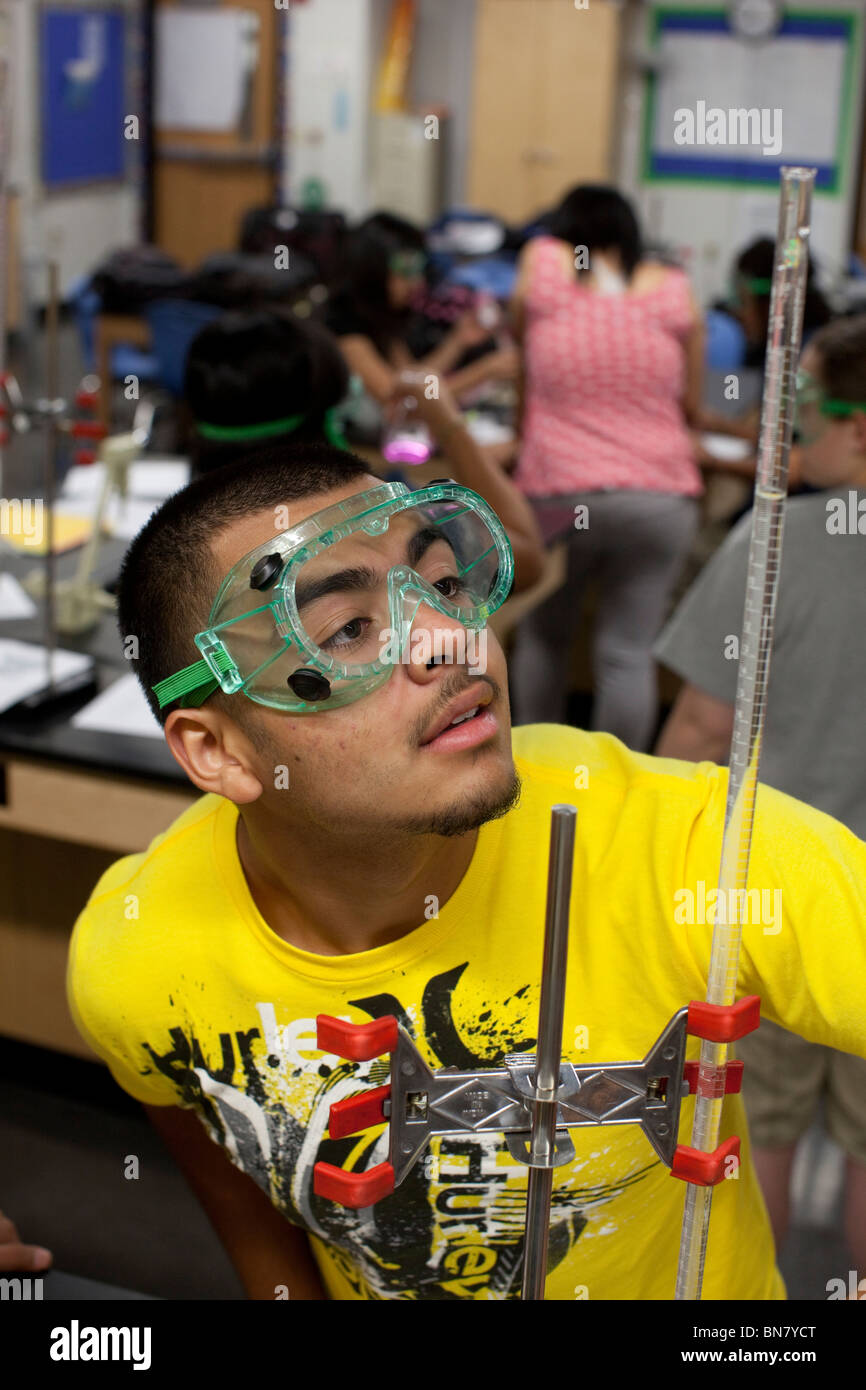 Hispanic male student wearing safety goggles watches solution in graduated cylinder during chemistry class Stock Photo