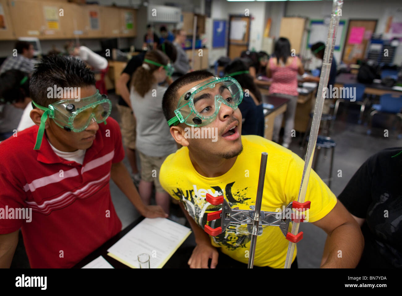 High school boys wearing safety goggles observe liquid in a graduated cylinder during a titration experiment in Stock Photo