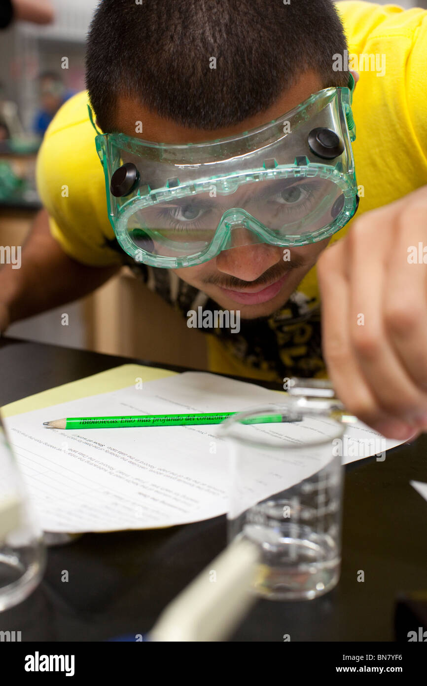 Hispanic male student wearing safety goggles pours solution from test tube into beaker during chemistry class Stock Photo