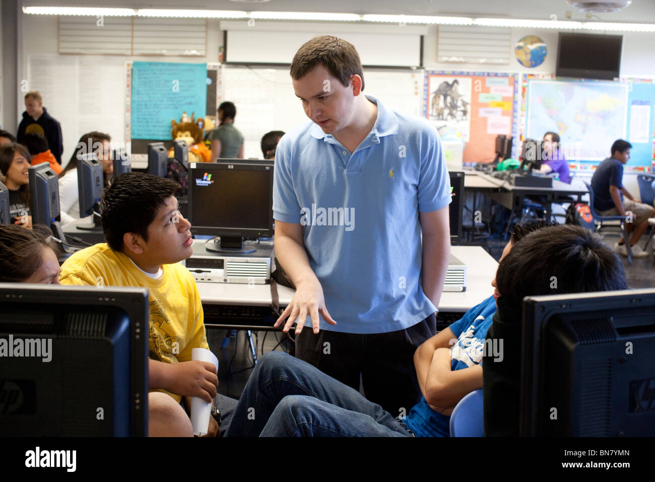 Anglo male high school English teacher talks to  students in classroom Stock Photo