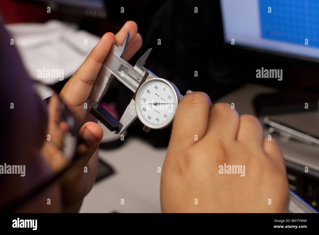 High school boy uses a caliper to take a measurement in freshman engineering class - Stock Image