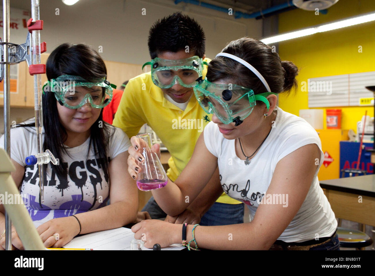 High school students wearing safety goggles observe liquid in a beaker during a titration experiment in chemistry Stock Photo