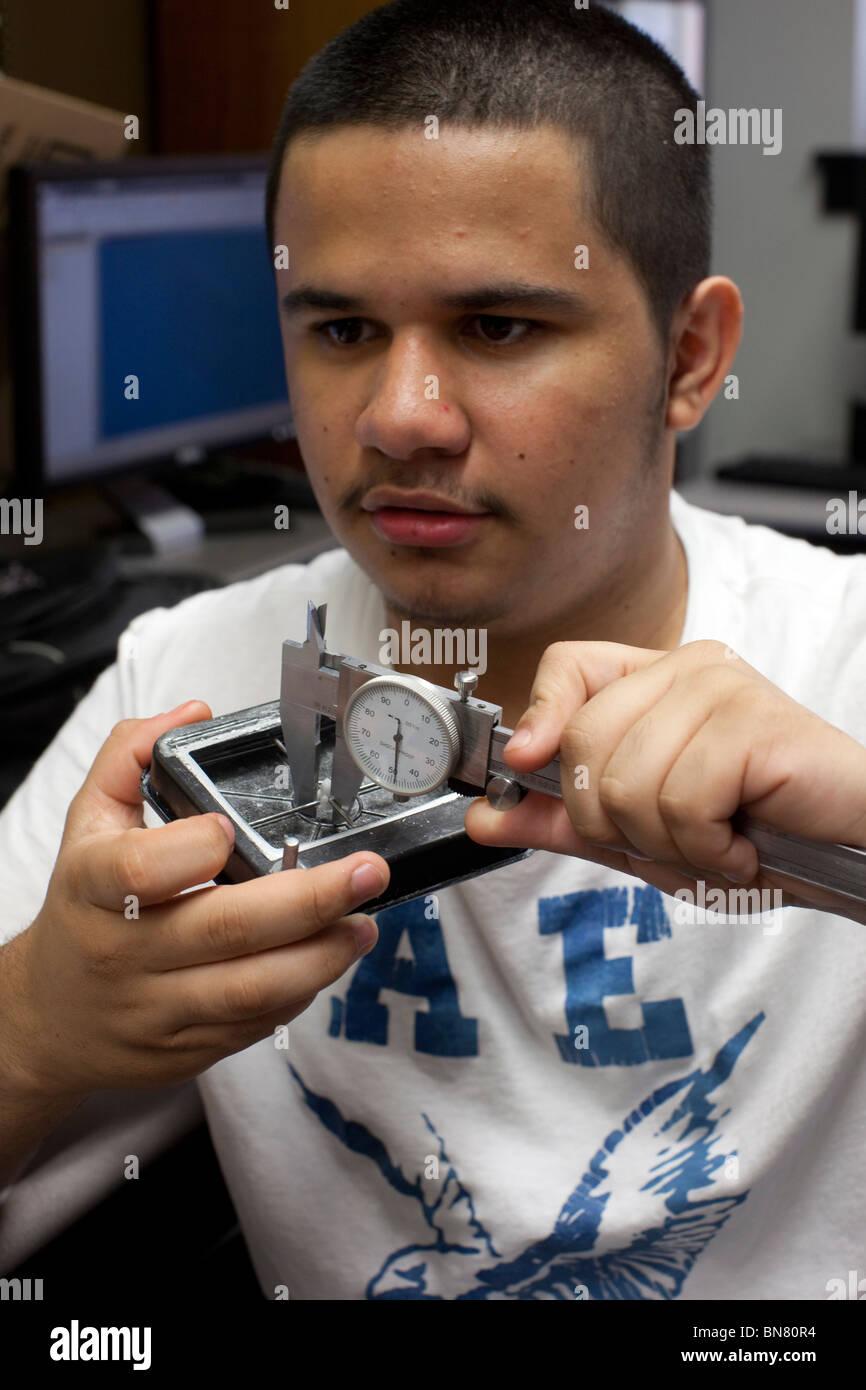Hispanic high school boy uses a caliper to take a measurement in freshman engineering class Stock Photo