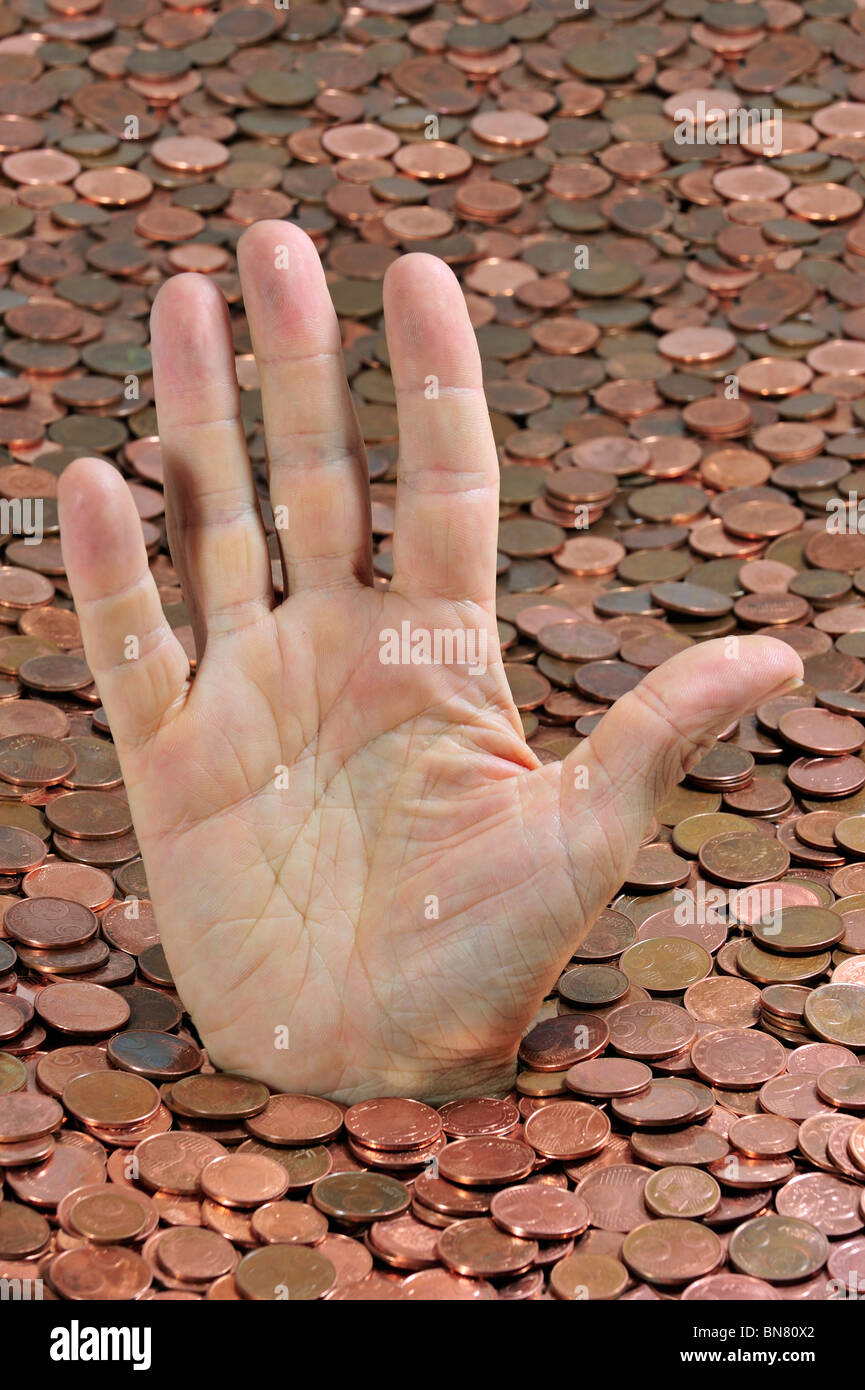 Man disappearing in euro coins while sticking hand out because of debt during crisis in the European Union in Europe - Stock Image