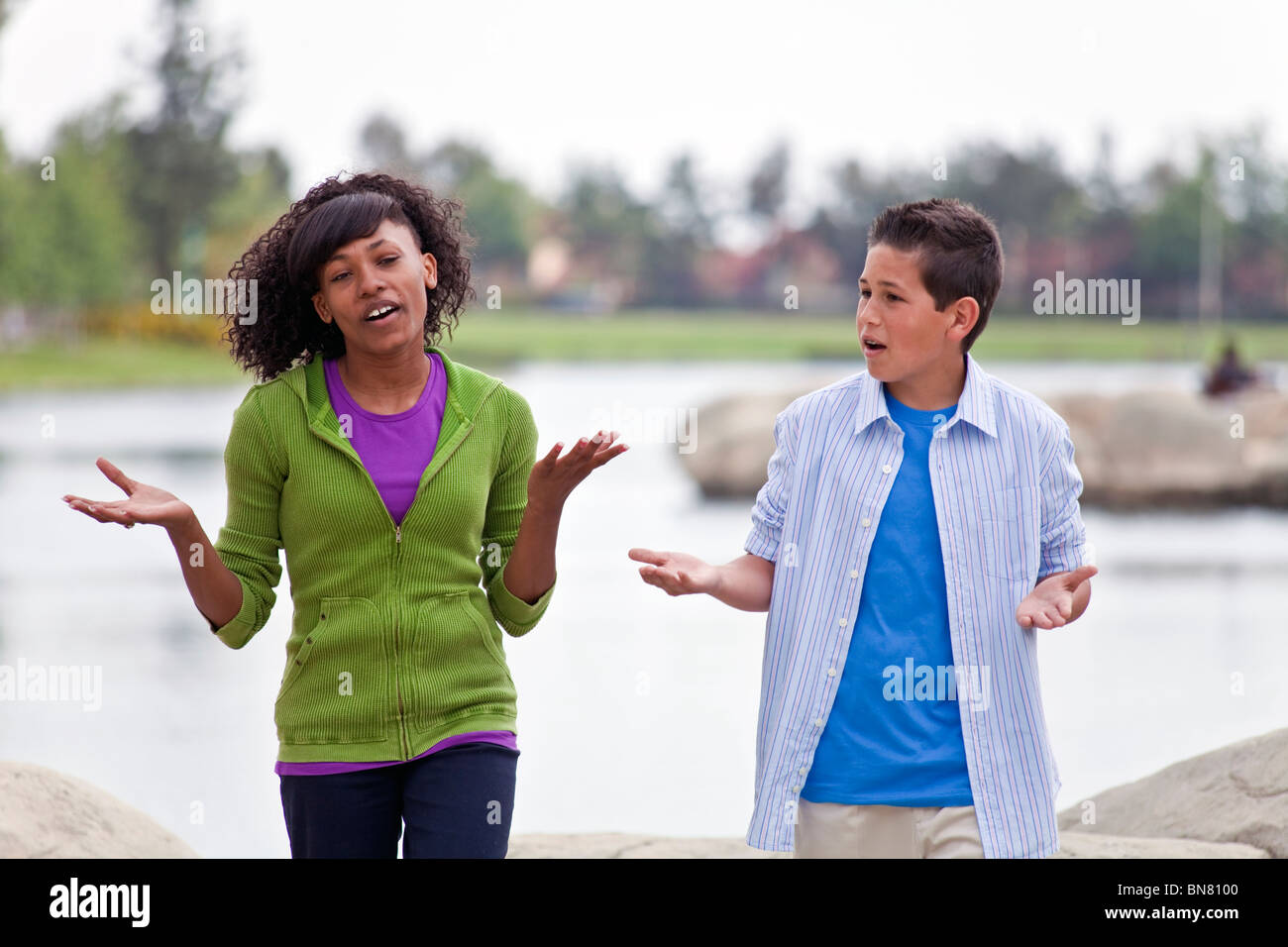 Multi ethnic racial Ethnically diverse teens 14-16 year old African American Girl and Caucasian boy talking.MR Myrleen - Stock Image