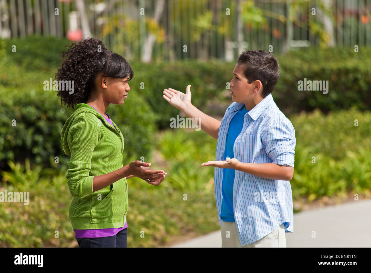 California Multi ethnic racial Ethnically diverse group teenagers African American teens talking enthusiastic conversation - Stock Image