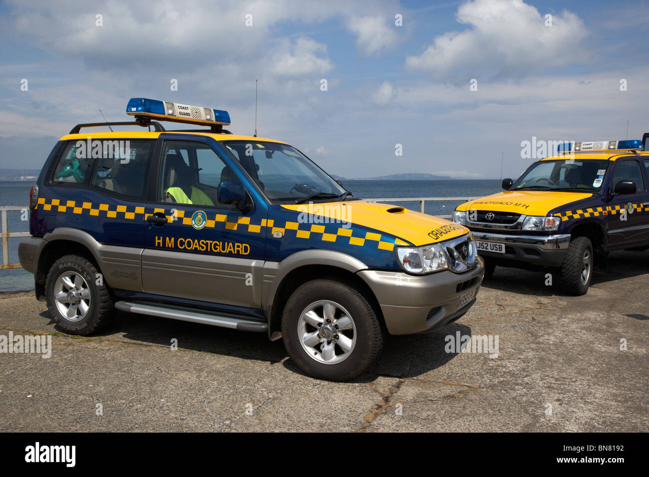 two HM Coastguard search and rescue 4x4 vehicles parked on a pier in the uk - Stock Image