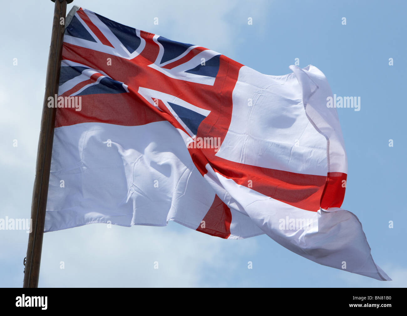 Royal Navy white ensign as flown from the back of a warship in the UK - Stock Image