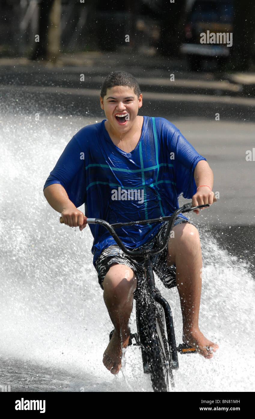 A young teen rides his bicycle through a stream of water from a fire hydrant during a heat wave in CT USA - Stock Image