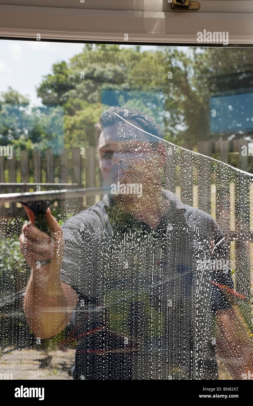 Window cleaner man cleaning outside windows wiping soap suds with squeegee seen through glass from inside - Stock Image