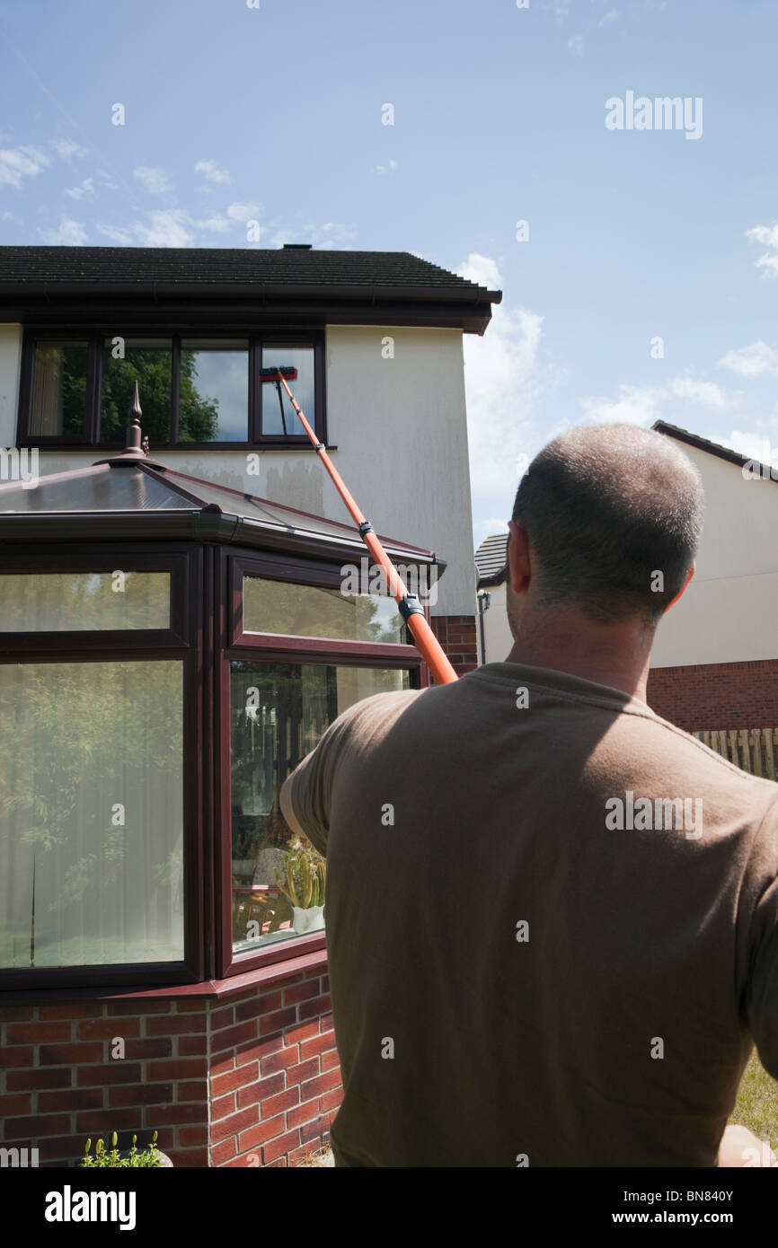 Window cleaner using a soapless pure water fed long pole and brush window cleaning system to clean windows above - Stock Image