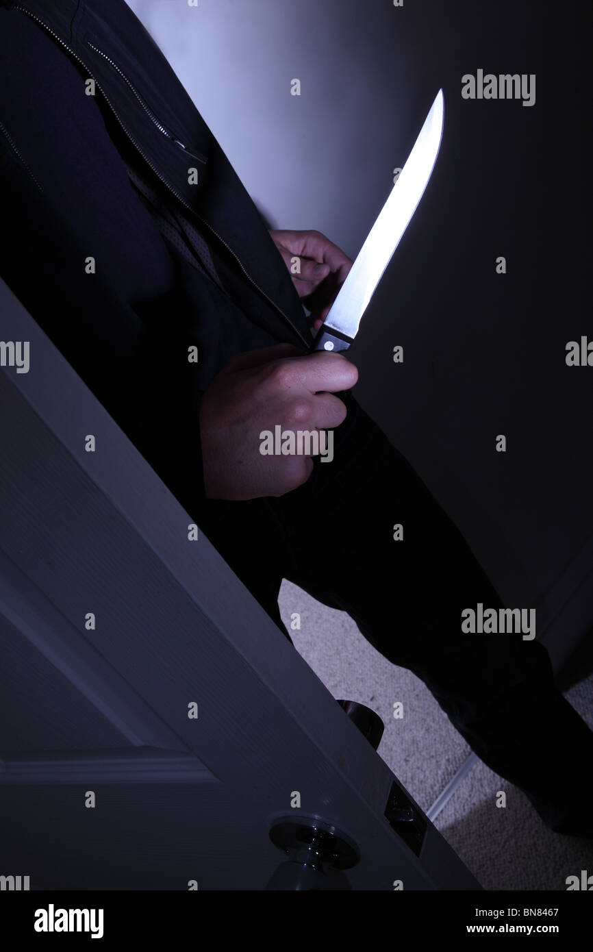 Man with a knife entering a dark room - Stock Image