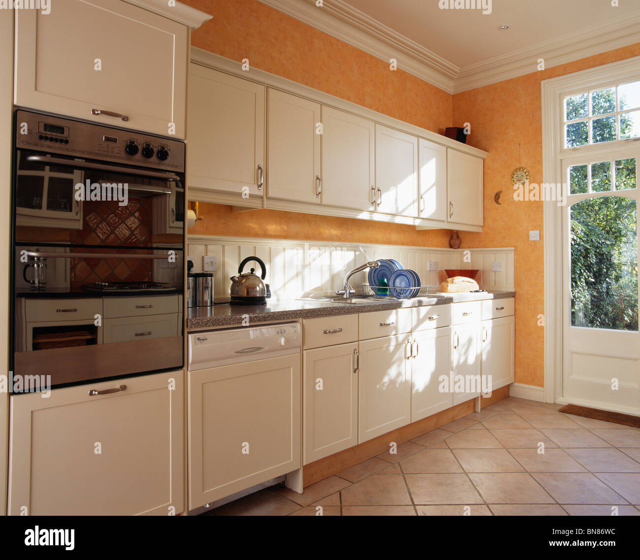 Orange Kitchen Room With White Cabinets Stock Image: Eye-level Oven In Modern Orange Kitchen With White Fitted