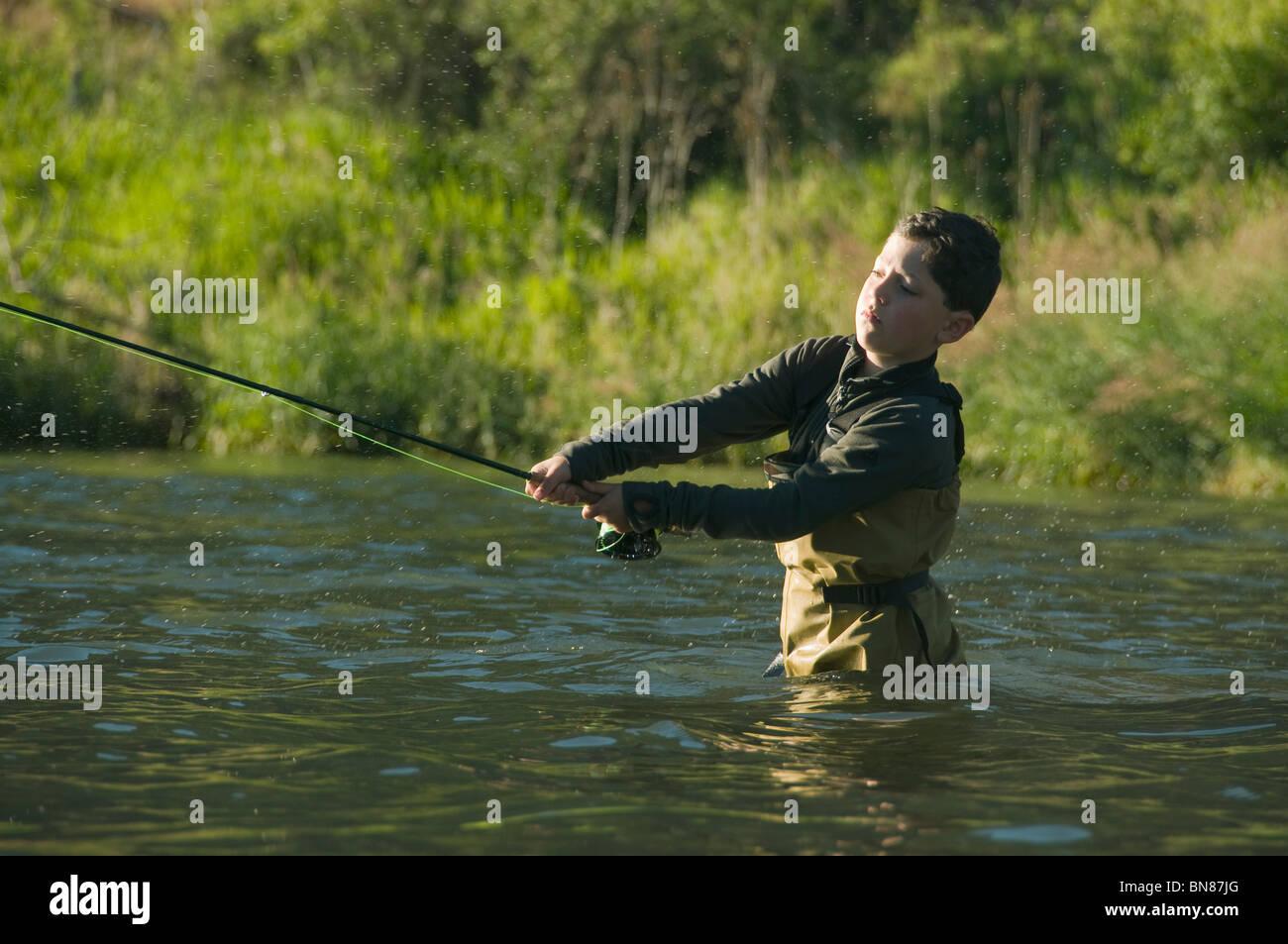 Boy, aged 8, fly-fishing, Deschutes River, Oregon - Stock Image