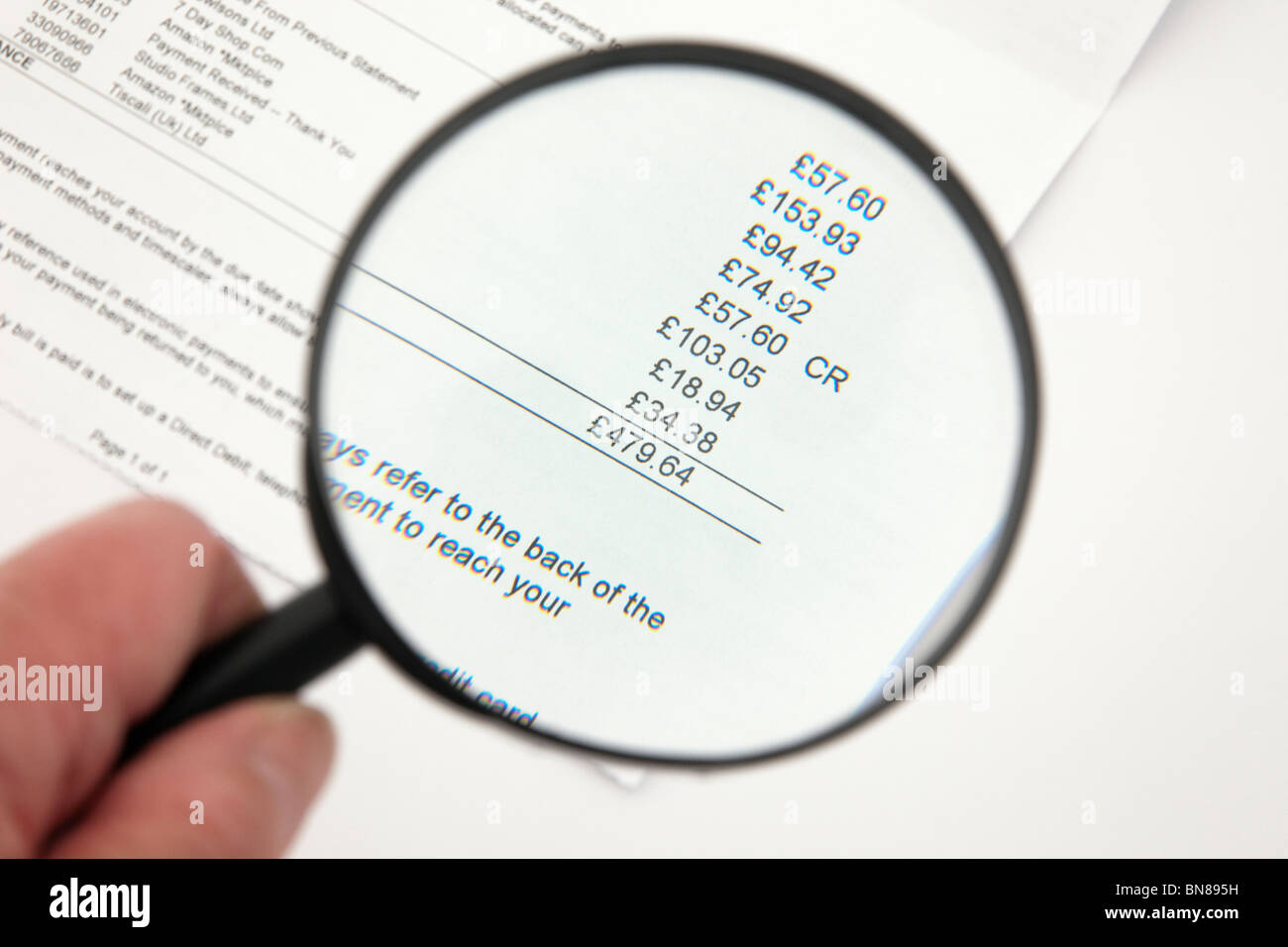 Person holding a magnifying glass to look at a large credit card bill. - Stock Image