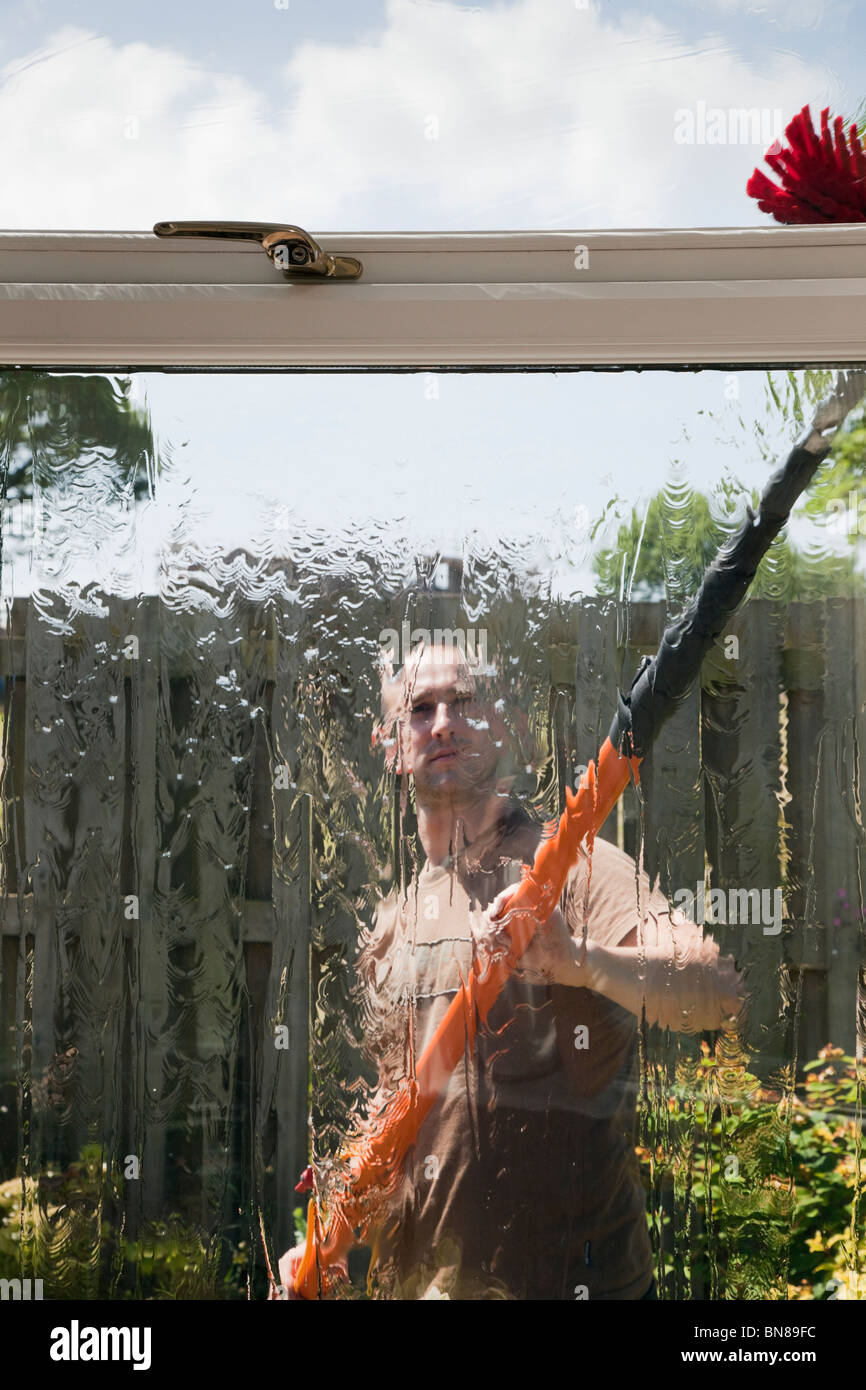 Window cleaner outside using a soapless pure water fed pole and brush window cleaning system for clean glass seen - Stock Image