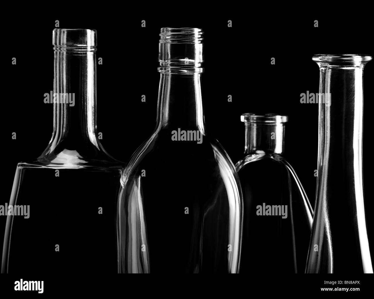 Abstract transparent glass bottle on black with reflection - Stock Image