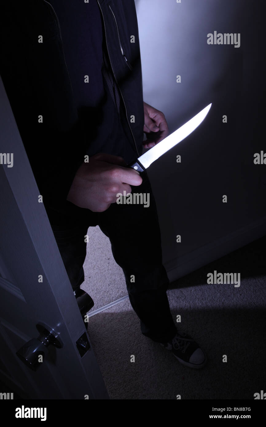 Dark figure of a man entering a room holding a knife. - Stock Image